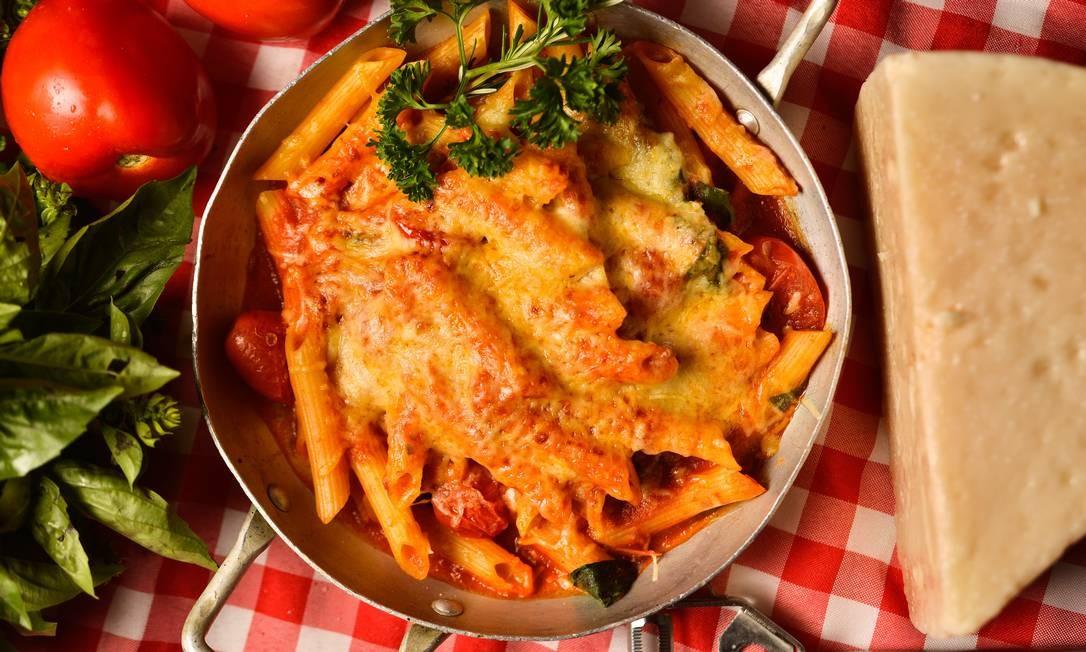 Nas compras acima de R$ 60, o da Carmine (3617-6109) envia de brinde uma pasta fresca para ser preparada em casa. Acima, uma das opções do menu: penne ao molho pomodoro, basílico e tomate-cereja gratinado no forno a lenha com mozarela: R$ 48,75 (para uma pessoa) e R$ 76,20 (para duas) Foto: Divulgação/Bruno de Lima