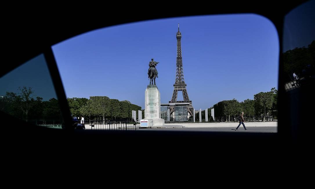 Homem caminha sozinho ao longo do Champ de Mars. Ao fundo, a Torre Eiffel Foto: CHRISTOPHE ARCHAMBAULT / AFP