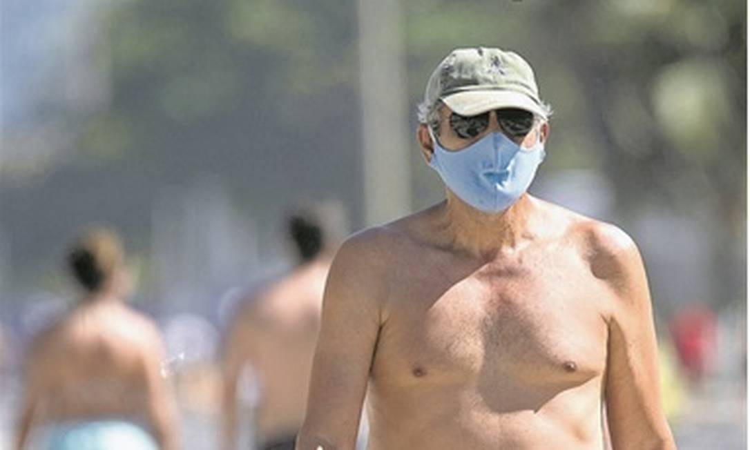 Homem caminha com máscara no calçadão de Copacabana: o uso do item é exigido em locais públicos Foto: Ana Branco / Agência O Globo