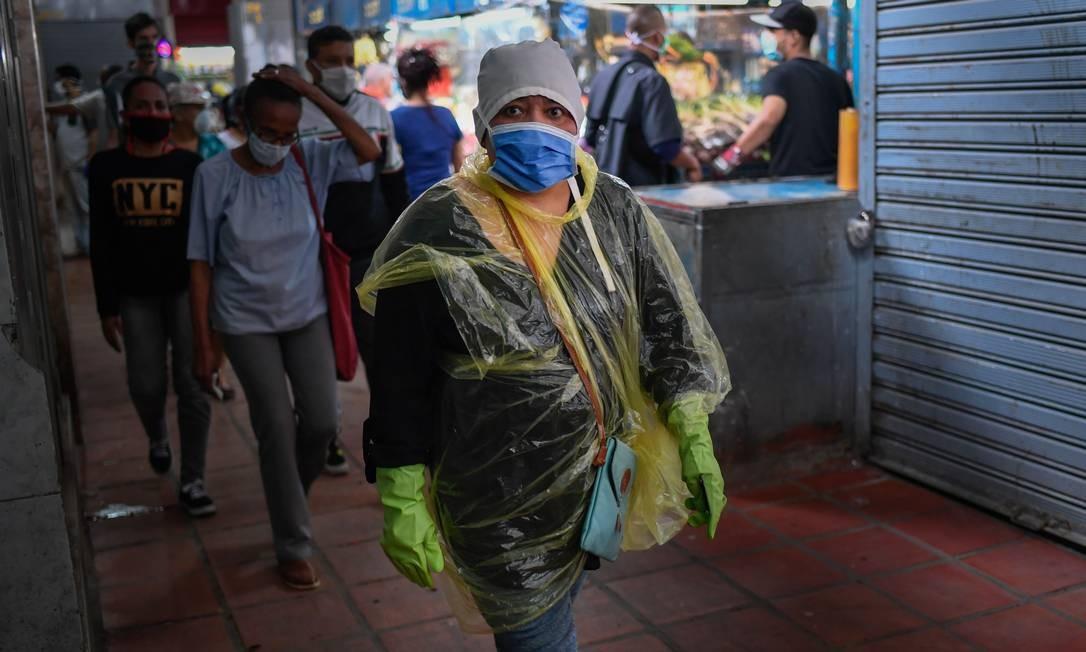 Mulher com máscara, luva e proteção caseiras caminha em mercado em Caracas Foto: FEDERICO PARRA / AFP