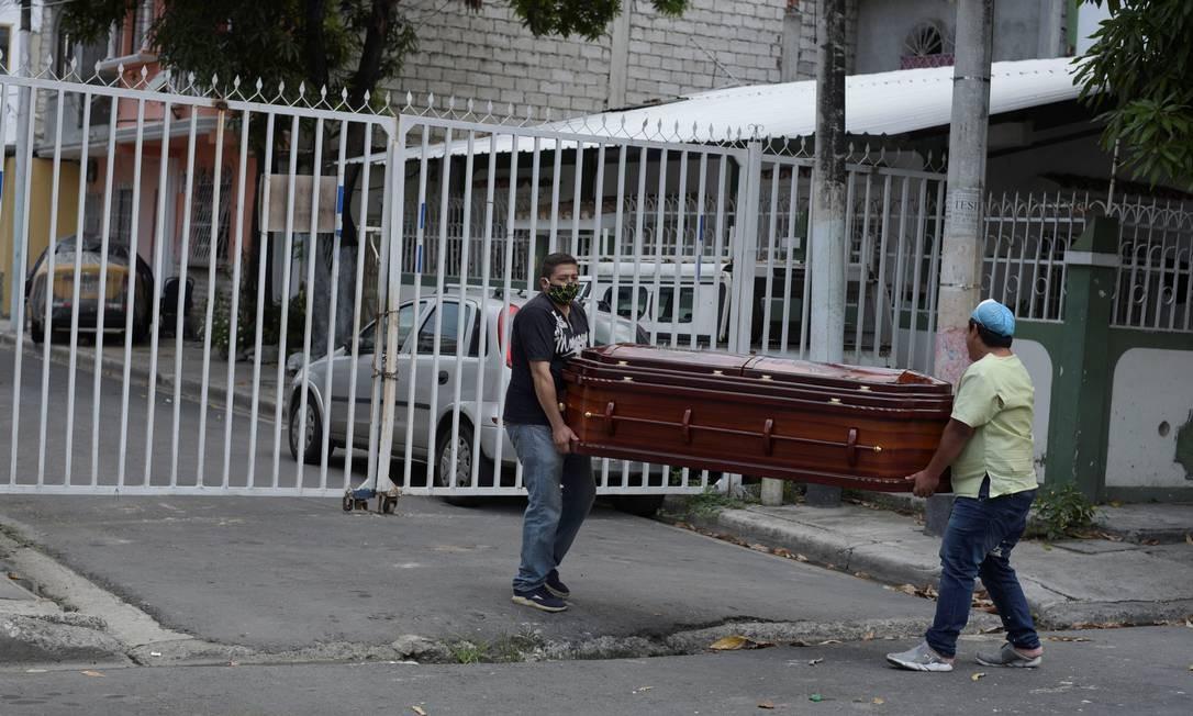 Membro da família e funcionário de funerária carregam caixão com o corpo de uma mulher que morreu em casa durante o surto de coronavírus em Guayaquil Foto: Vicente Gaibor del Pino / Reuters/31-03-2020