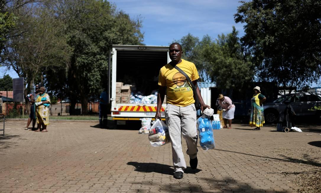 Homem com camiseta do presidente Cyril Ramaphosa busca alimentos em um posto do governo destinado à população vulnerável Foto: Siphiwe Sibeko / REUTERS