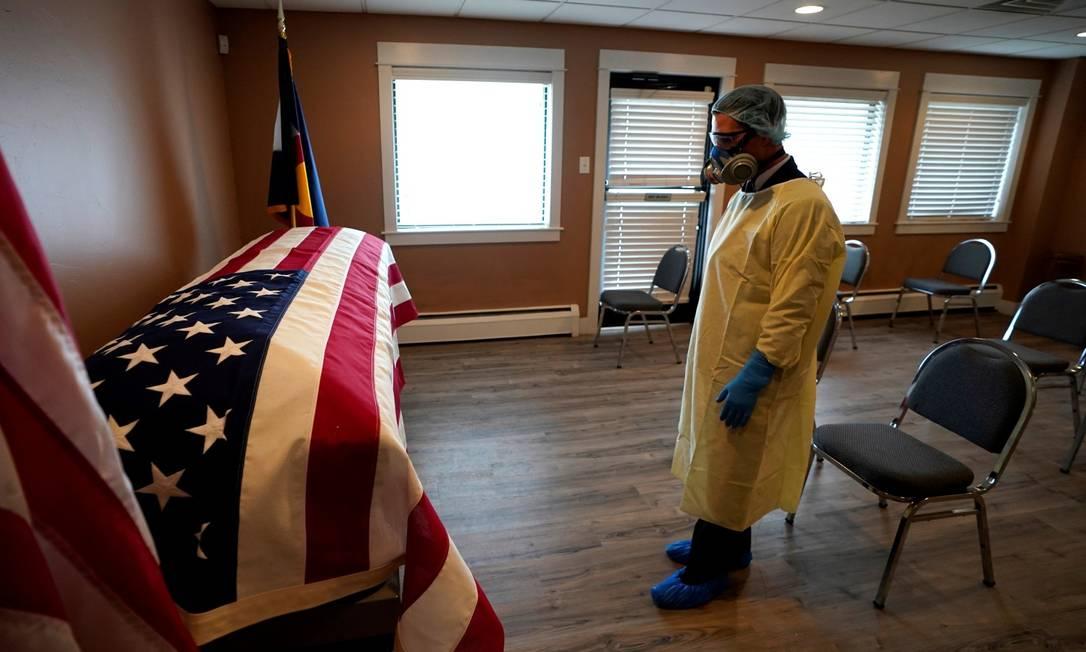 Diretor de funerária observa caixão de George Trefrene, veterano da Guerra da Coreia, que morreu aos 90 anos de Covid-19 Foto: RICK WILKING / REUTERS / 23-04-2020
