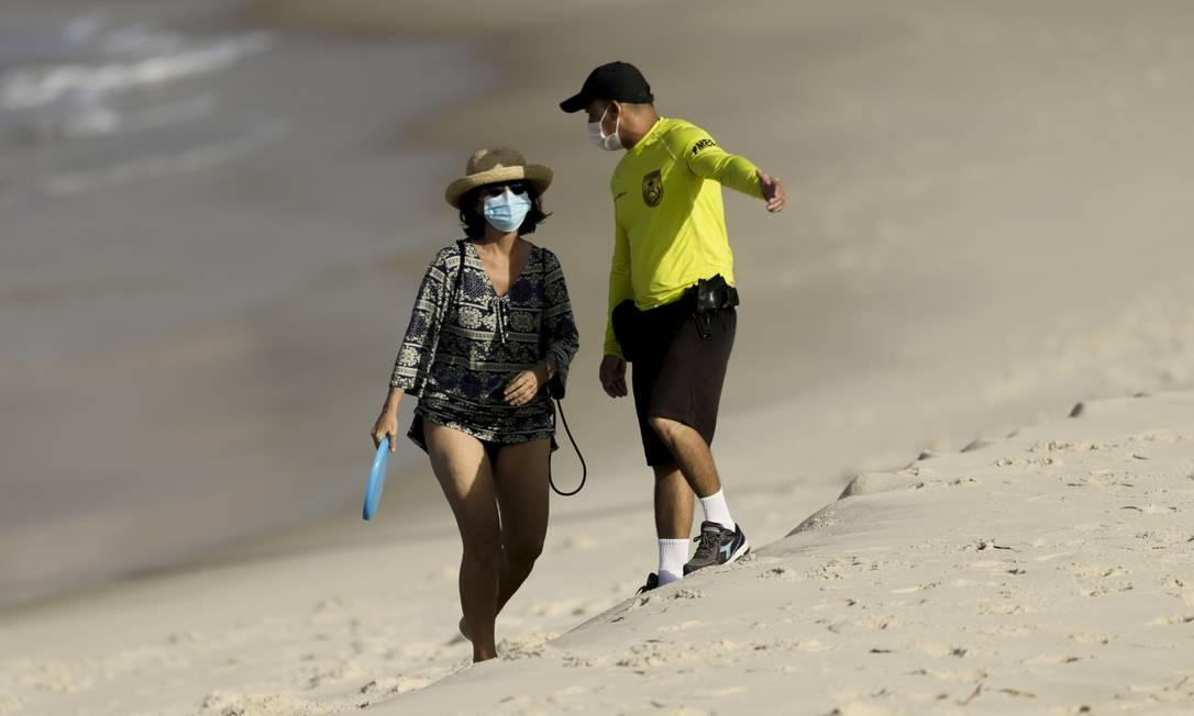 Pandemia de coronavírus: cariocas aderem ao uso de máscaras no primeiro dia útil de exigência. No Arpoador polícia convida mulher a sair da areia Foto: Gabriel de Paiva / Agência O Globo