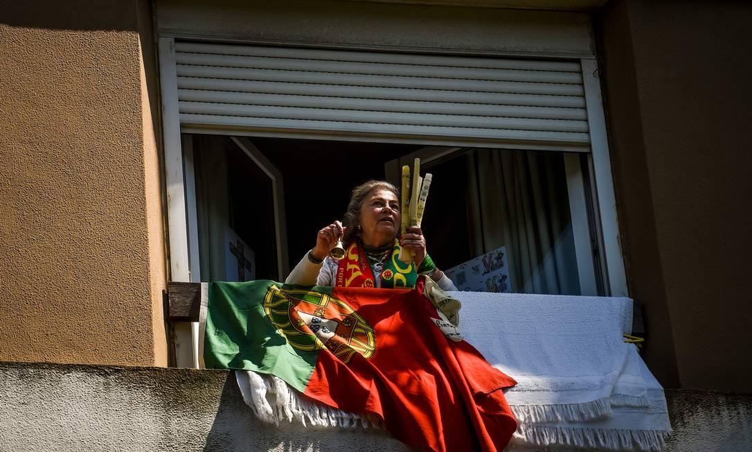 Mulher na janela com a bandeira de Portugal, em Lisboa Foto: PATRICIA DE MELO MOREIRA / AFP