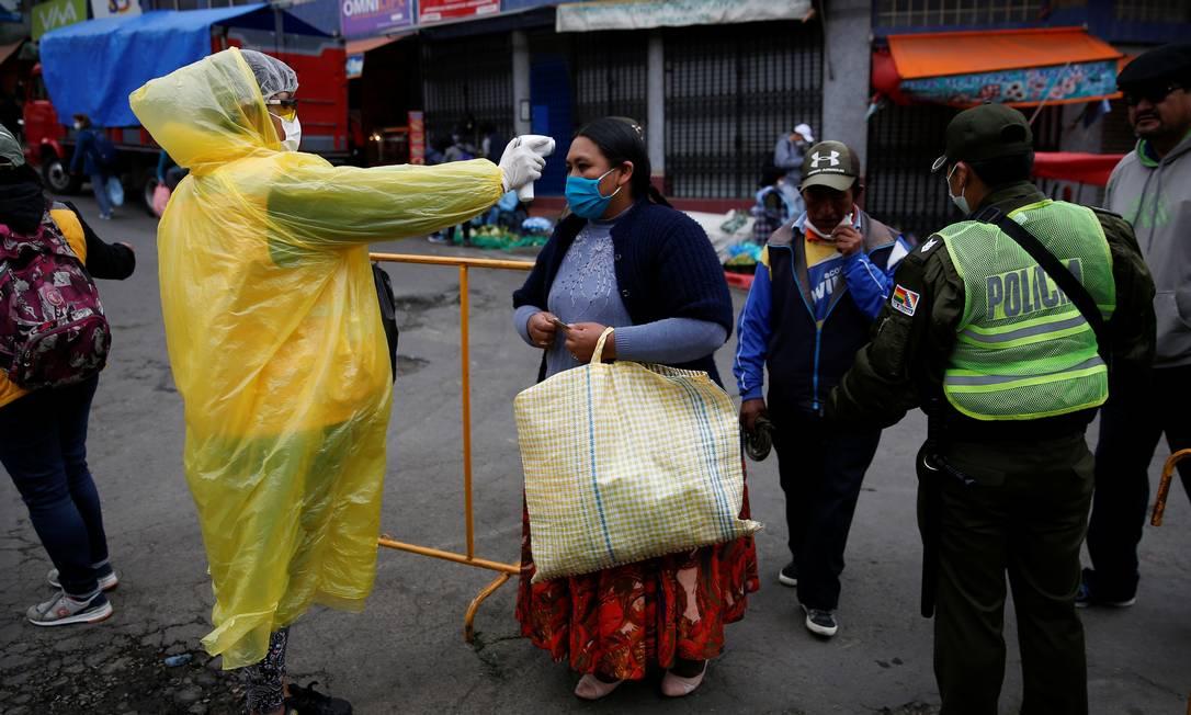 Profissional de saúde mede temperatura de pessoas na capital boliviana La Paz. Quarentena no país fica em vigor até 30 de abril, mas pode ser estendida Foto: DAVID MERCADO / Reuters