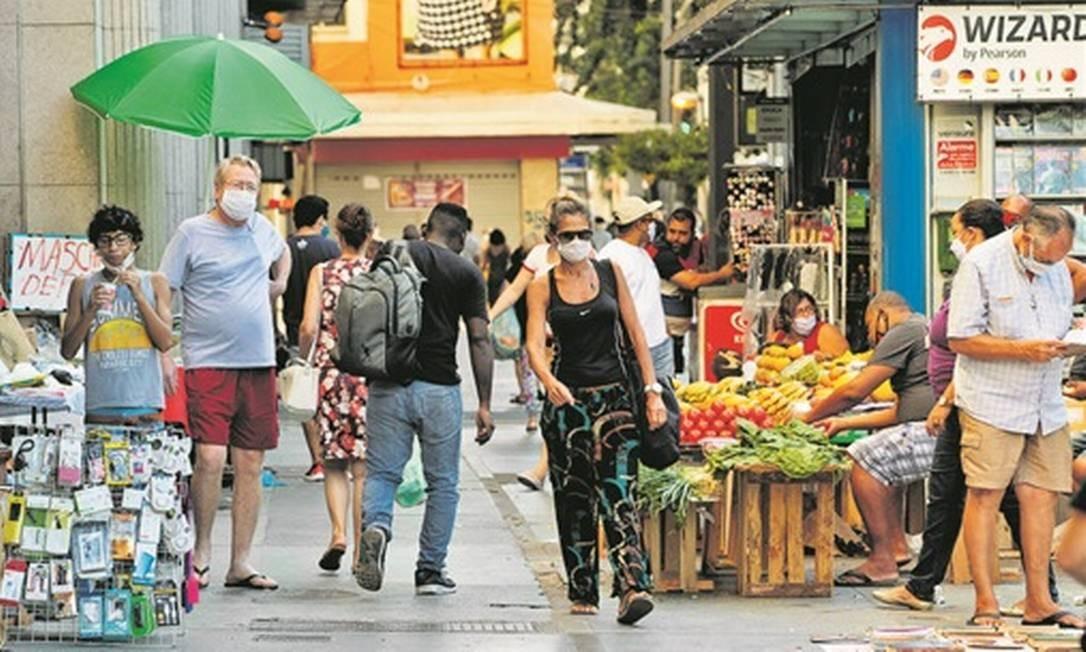 Pedestres e ambulantes tomam a calçada no Largo do Machado: se não fossem as máscaras, movimentação pareceria a de dias antes da pandemia Foto: Agência O Globo / Roberto Moreyra