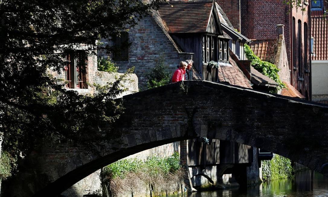 Um casal atravessa uma ponte no centro histórico de Bruges Foto: Francois Lenoir / Reuters
