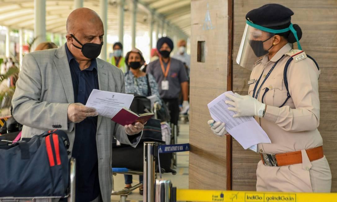 Equipe de segurança checa documentos de passageiros de voo especial da Índia para o Reino Unido, em meio a temores pela pandemia Foto: NARINDER NANU / AFP