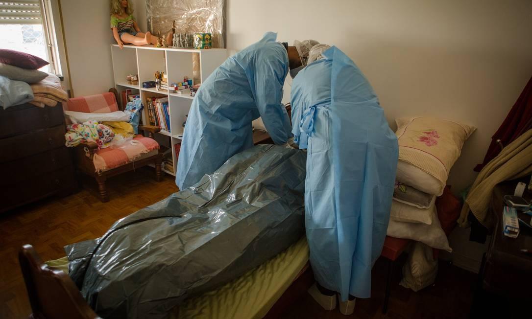 Socorristas do Samu preparam cadáver de mulher idosa que morreu com suspeita de estar contaminada pelo novo coronavírus Foto: Yan Boechat