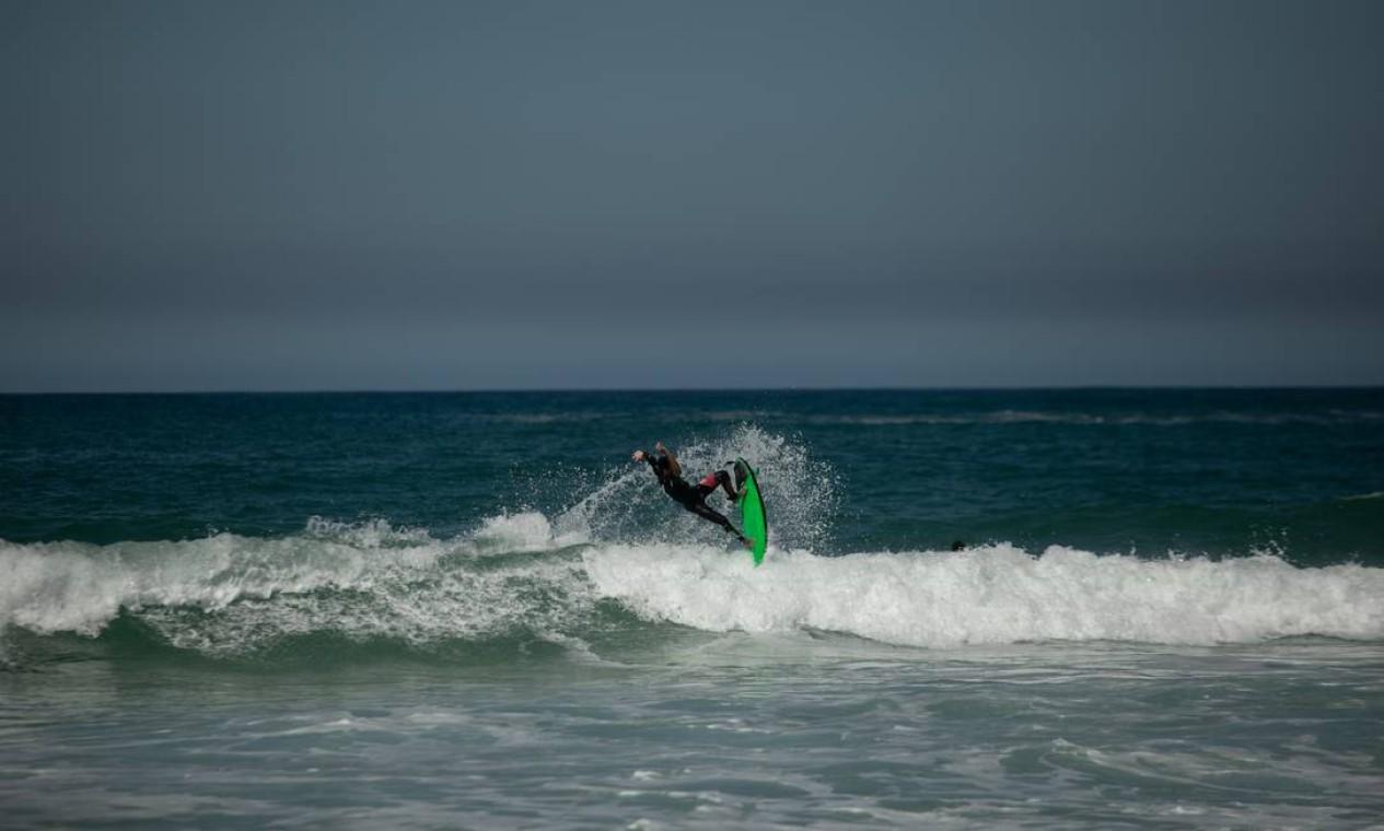 Um surfista pega onda na Praia do Recreio Foto: BRENNO CARVALHO / Agência O Globo