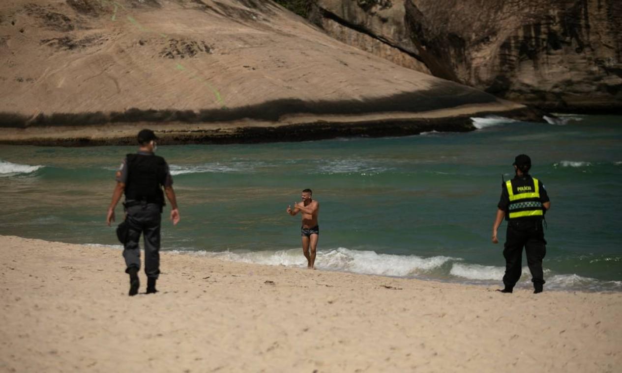 Apesar do policiamento no Recreio, muitos banhistas ignoraram decreto que proibe o acesso às praias e entraram no mar Foto: BRENNO CARVALHO / Agência O Globo
