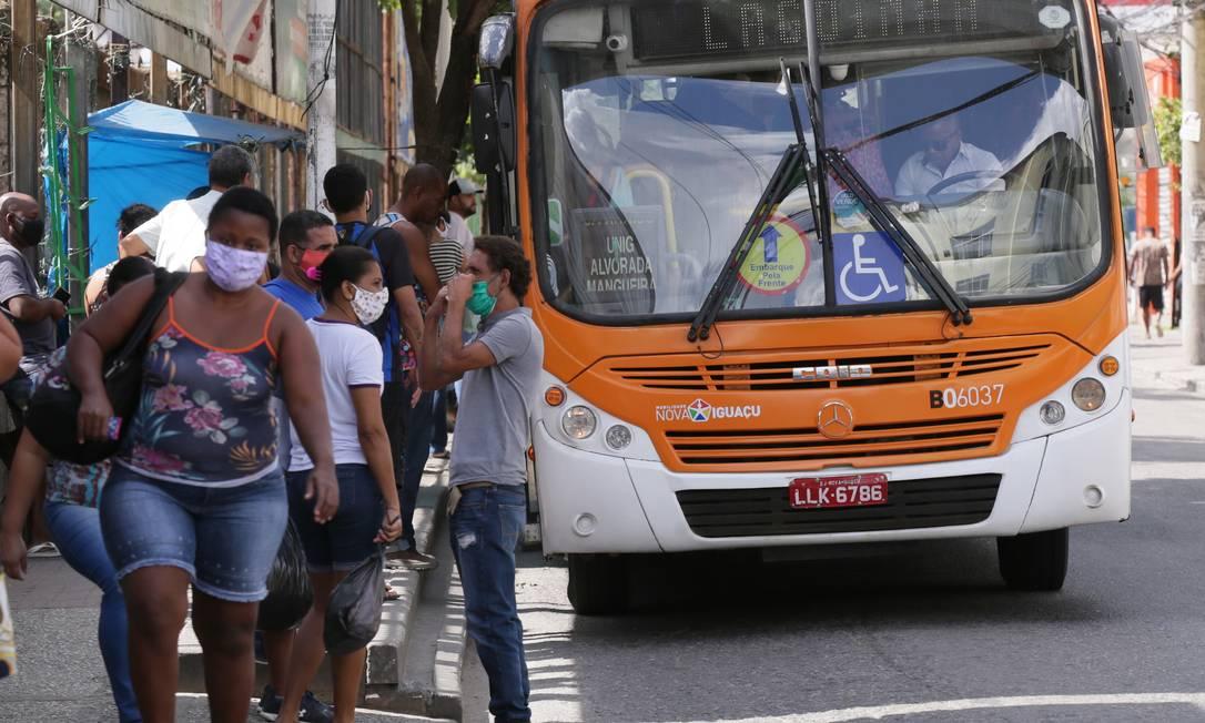 Trabalhadores se movimentam em ponto de ônibus de Nova Iguaçu; isolamento divide brasileiros Foto: Cléber Júnior / Agência O Globo
