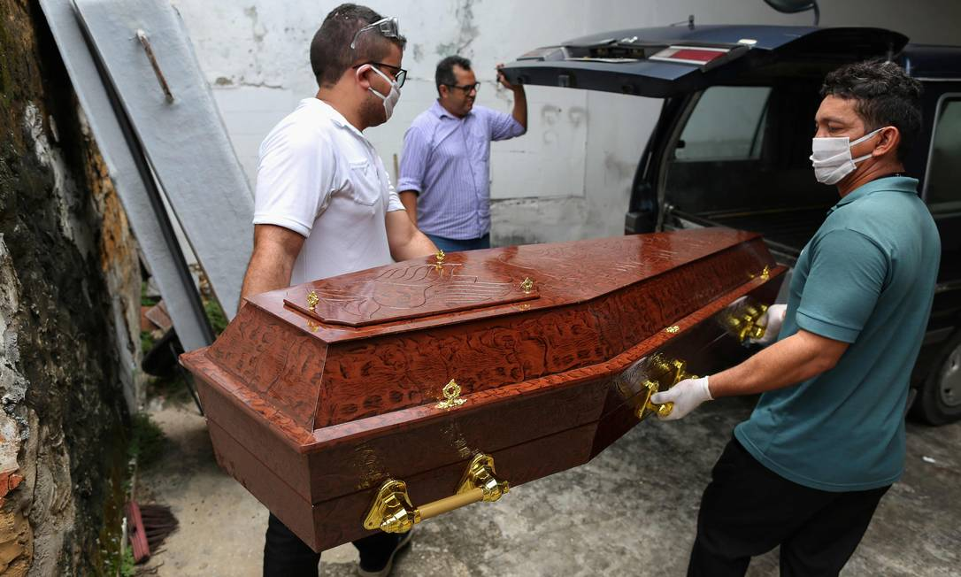 Funcionários de uma funerária de Manaus usam máscaras e luvas para carregar um caixão durante a pandemia do coronavírus. Foto: MICHAEL DANTAS / AFP