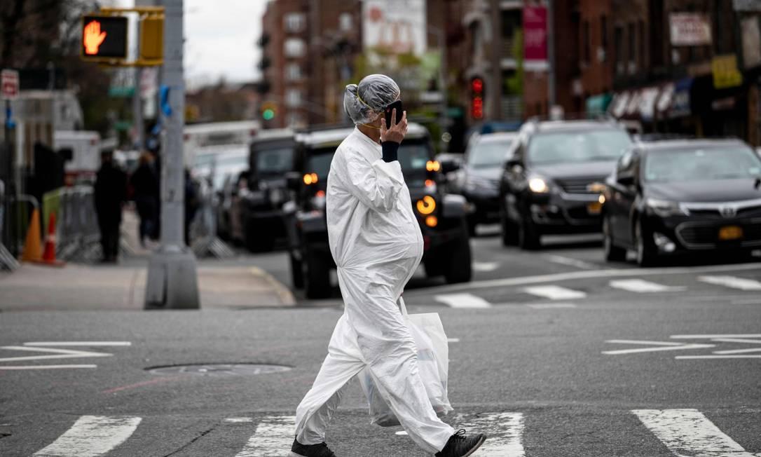 Grávida com roupa de proteção atravessa rua no Queens, em NY Foto: JOHANNES EISELE / AFP