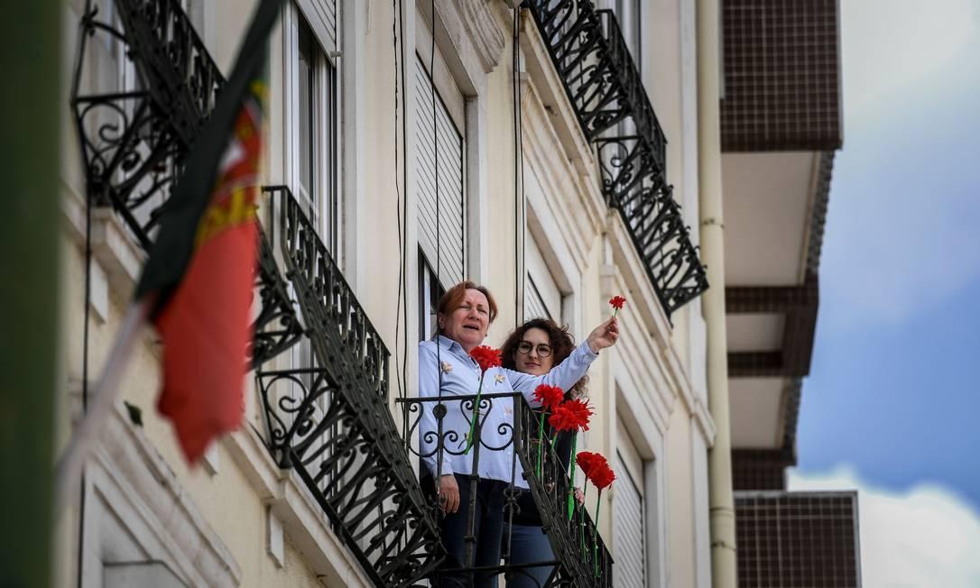 Cidadãos portugueses celebram o 46º aniversário da Revolução dos Cravos de suas janelas durante a pandemia do novo coronavírus Foto: Patricia de Melo Moreira / AFP