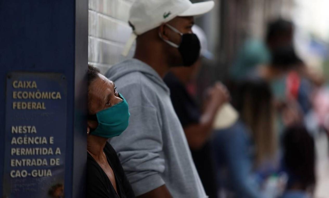Sem distância segura umas das outras, pessoas aguardam na fila da agência da Caixa na Rua Lopes Trovão, em Icaraí, Niterói Foto: FABIO MOTTA / Agência O Globo - 28/04/2020