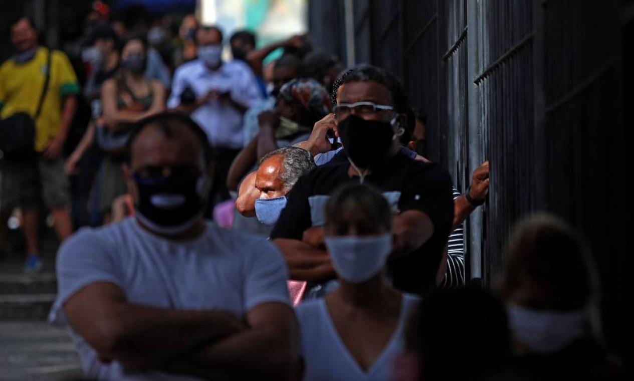 Pessoas aguardam em fila da agência da Caixa Econômica da Rua Riachuelo, na Lapa, centro do Rio. A Caixa creditou o auxílio emergencial de R$ 600 para 5,1 milhões de pessoas Foto: FABIO MOTTA / Agência O Globo
