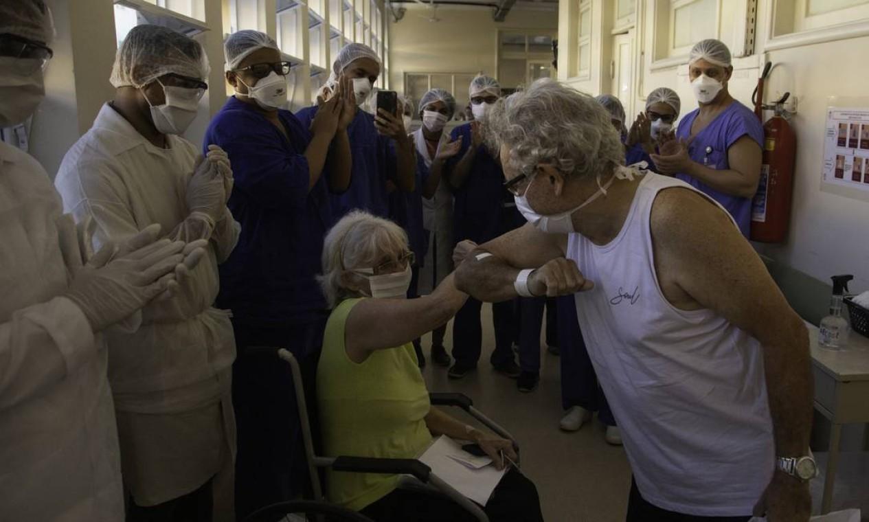 De pé, Almir cumprimenta Marlene, com quem é casada há 48 anos, com o cotovelo Foto: Gabriel Monteiro / Agência O Globo