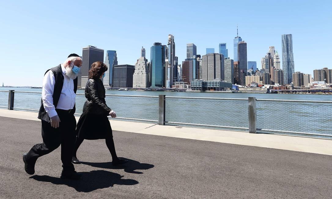 Casal caminha no Brooklyn, em Nova York, usando máscaras: um dos maiores centros financeiros do mundo está paralisado há semanas Foto: AL BELLO / AFP