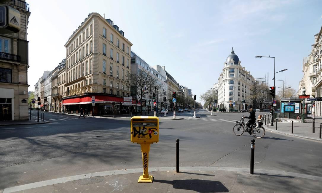 Um ciclista passa pelas vias desertas de Grands Boulevards, em Paris, próximo a um bloqueio instalado para tentar diminuir o avanço da Covid-19 na França Foto: Charles Platiau / Reuters