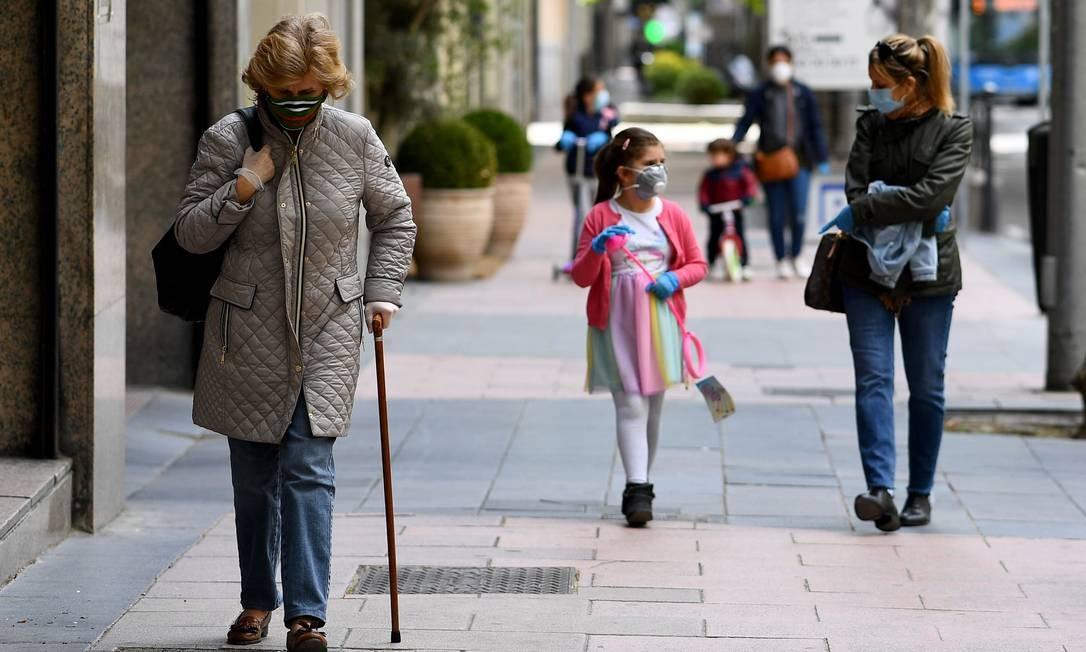 Pessoas usando máscaras caminham pelas ruas de Madri: governo espanhol anunciou que o confinamento será progressivamente flexibilizado nas próximas semanas, em quatro etapas Foto: Gabriel Bouys / AFP