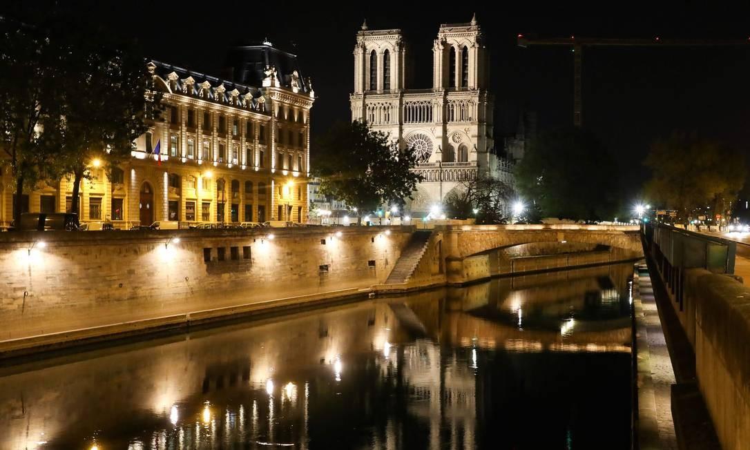 Vista geral da Catedral de Notre Dame refletida no rio Sena, em Paris, à noite, durante as determinações de isolamento social para impedir a propagação da COVID-19 Foto: Ludovic MarinN / AFP