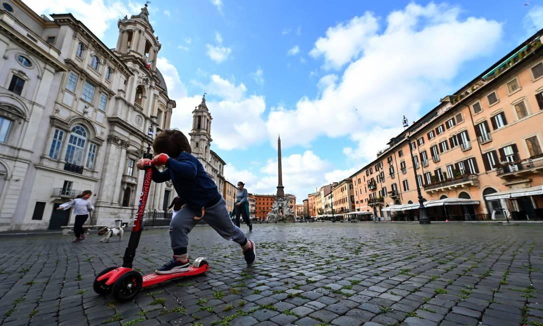Uma criança anda de patinete na Piazza Navona, em Roma Foto: Andreas Solaro / AFP
