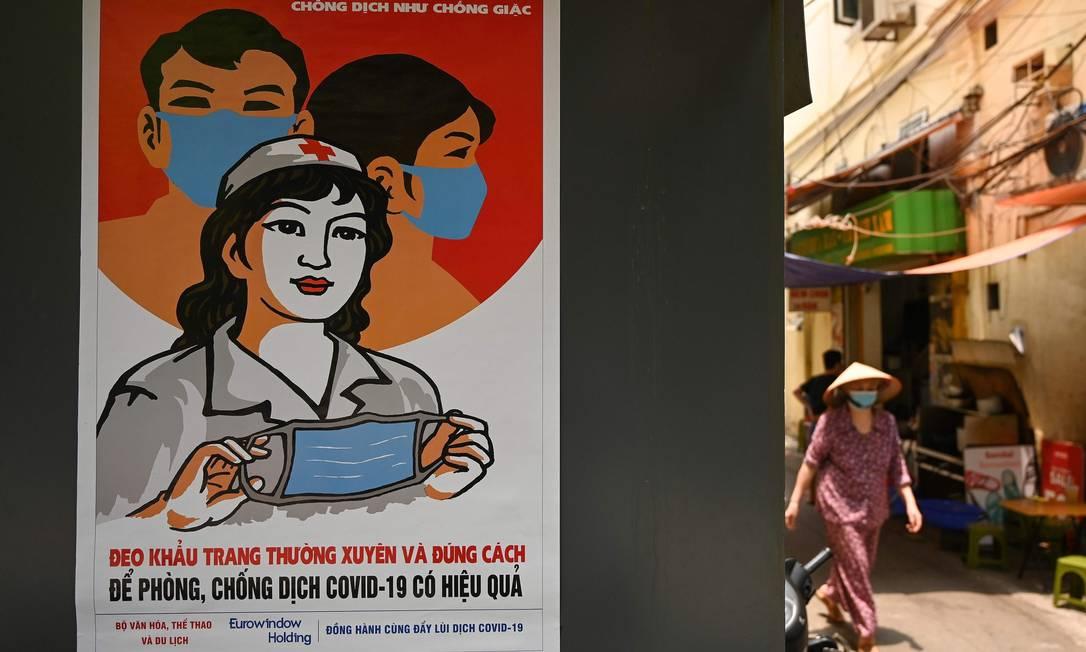 Propaganda do governo vietnamita para o uso obrigatório de máscaras no país Foto: MANAN VATSYAYANA / AFP