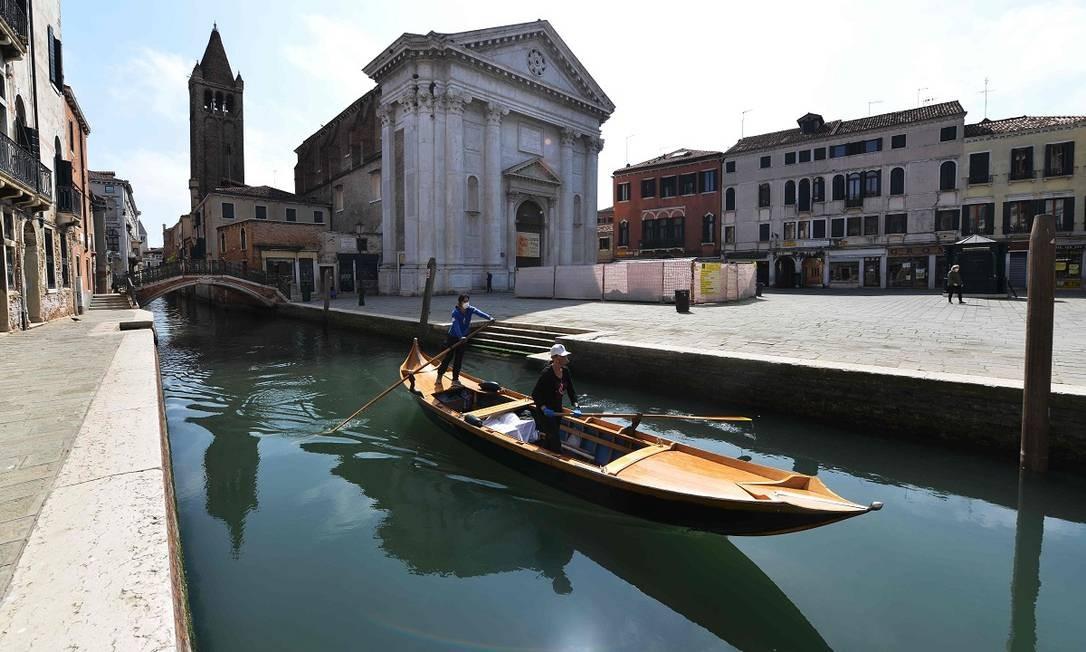 Duas mulheres, integrantes do grupo Row Venice, circulam pelos canais de Veneza, onde estão fazendo delivery em gôndolas para moradores que não podem sair de casa Foto: Andrea Pattaro / AFP