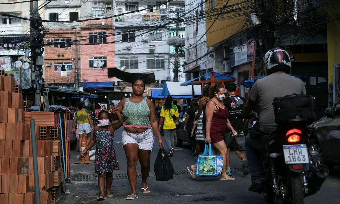 Moradores da Rocinha circulam com máscaras de proteção por ruas da comunidade Foto: RICARDO MORAES / REUTERS