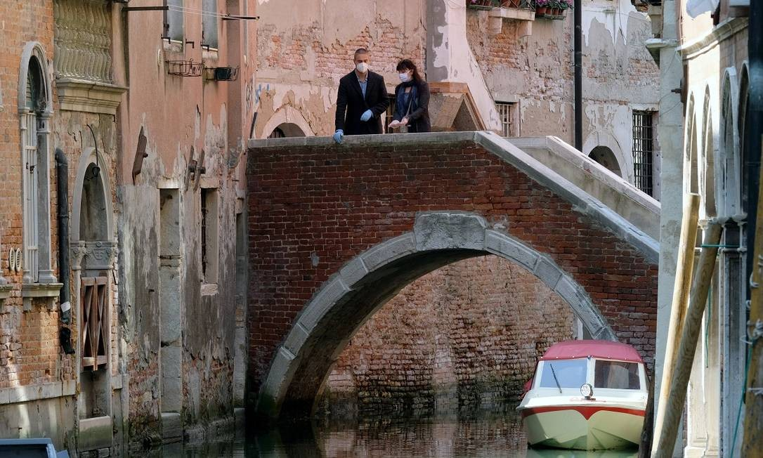 Pessoas usando máscaras e luvas numa ponte de Veneza Foto: Manuel Silvestri / Reuters