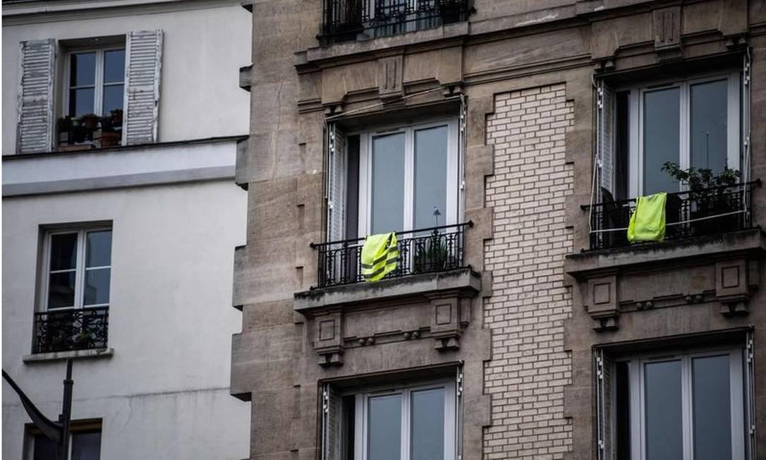 Coletes amarelos são pendurados em varandas, neste 1º de Maio, em Paris, no 46º dia de um estrito bloqueio na França para conter a propagação do novo coronavírus. Os chamados 'coletes amarelos' protagonizaram violentos protestos desde o fim do ano passado contra medidas do governo francês Foto: AFP