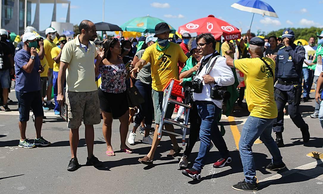 Enquanto o presidente esteve na rampa, jornalistas foram ameaçados e até agredidos por manifestantes. A PM interveio para retirá-los do local Foto: Jorge William / Agência O Globo