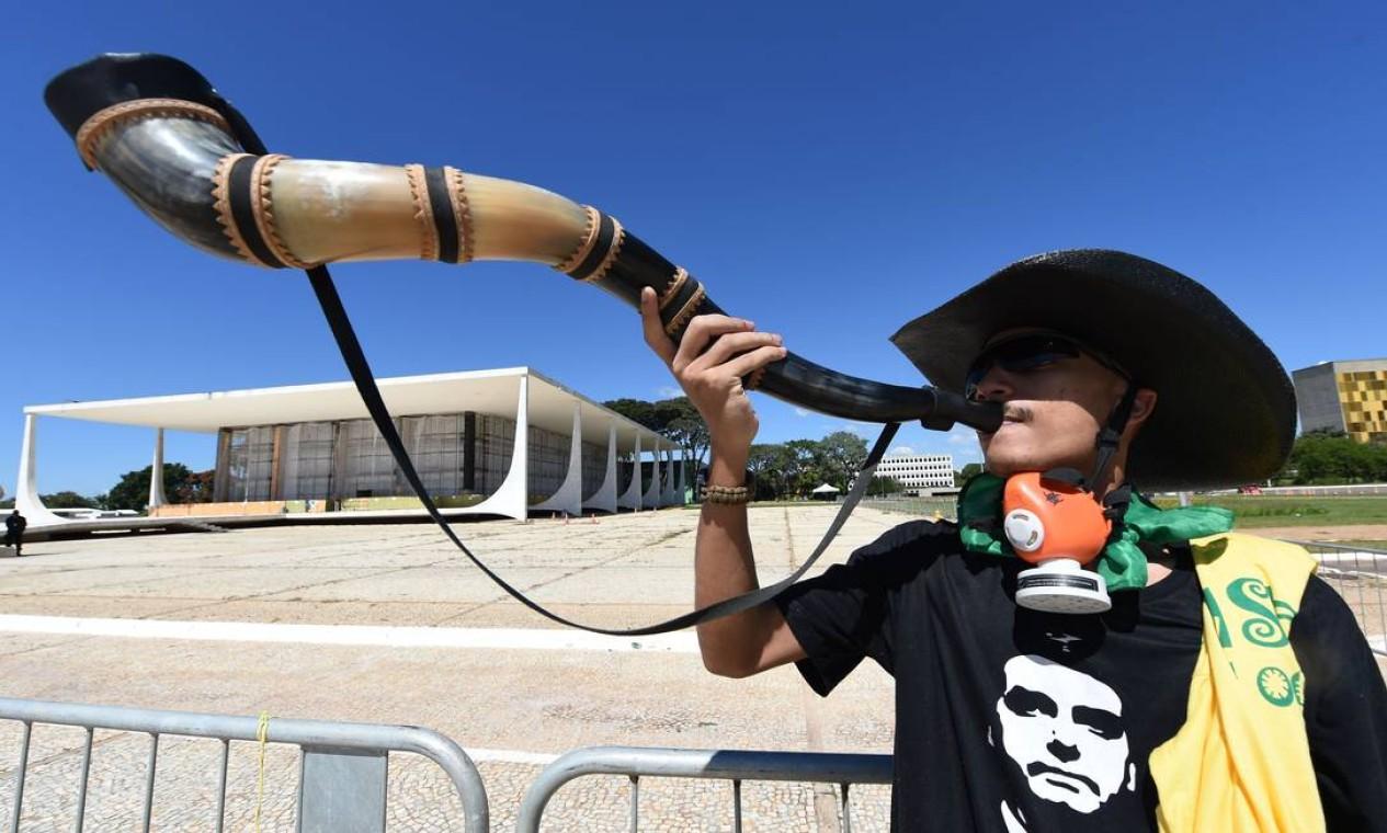 Partidário do presidente Jair Bolsonaro sopra um berrante durante manifestação de apoio ao governo na frente do STF, em Brasília, na manhã deste domingo Foto: EVARISTO SA / AFP