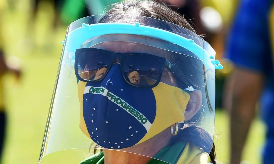 Apoiadora vestida com as cores verde e amarelo e usando máscaras de proteção participa de manifestação de apoio ao presidente Jair Bolsonaro, em Brasília Foto: EVARISTO SA / AFP