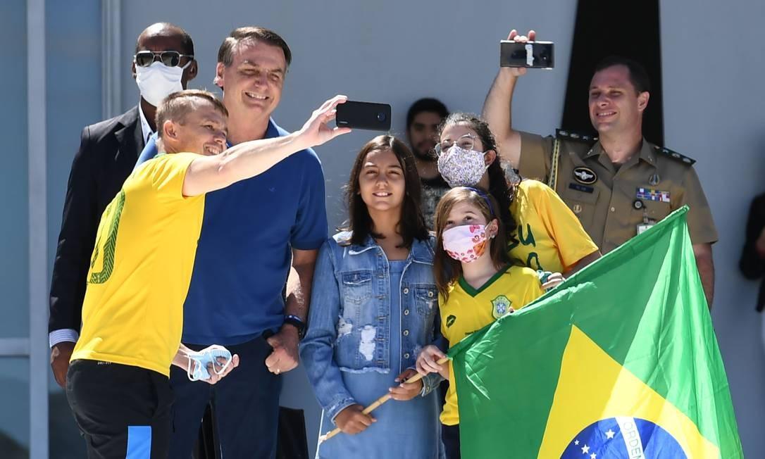 O presidente brasileiro Jair Bolsonaro e sua filha, Laura, posam para uma selfie com apoiadores, do lado de fora do Palácio do Planalto Foto: EVARISTO SA / AFP