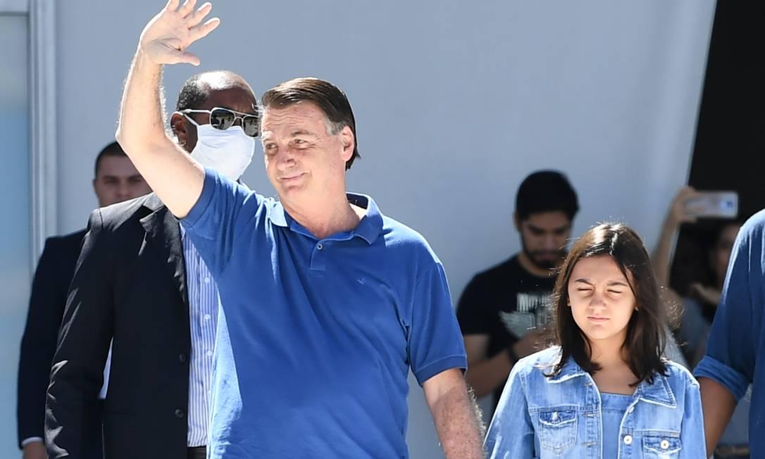 Ao lado da filha Laura, Bolsonaro, sem usar máscara de proteção, cumprimenta multidão presente Foto: EVARISTO SA / AFP