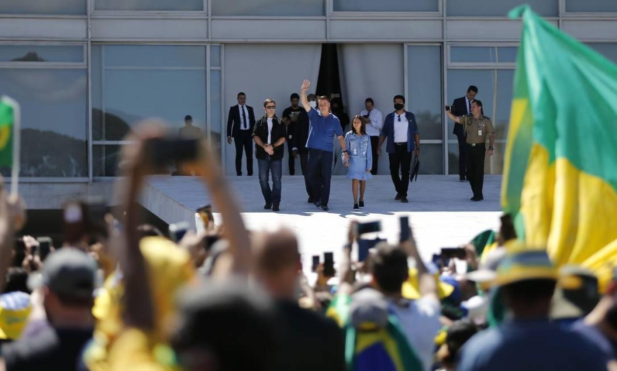 Na rampa do Palácio do Planalto, o presidente Jair Bolsonaro, acompanhado da filha Laura, acena para manifestantes que participam de manifestação antidemocrática em Brasília, emmaio. O presidente chegou a abraçar uma criança na rampa. Ele não se aproximou mais dos apoiadores por conta de duas grades de segurança que foram instaladas Foto: Jorge William / Agência O Globo - 03/05/2020
