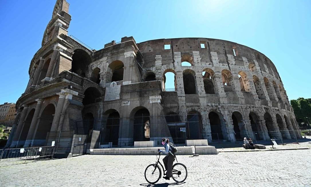 Mulher de bicicleta passa pelo Coliseu, em Roma: mortes em março aumentaram quase 50% em relação a 2019 Foto: VINCENZO PINTO / AFP