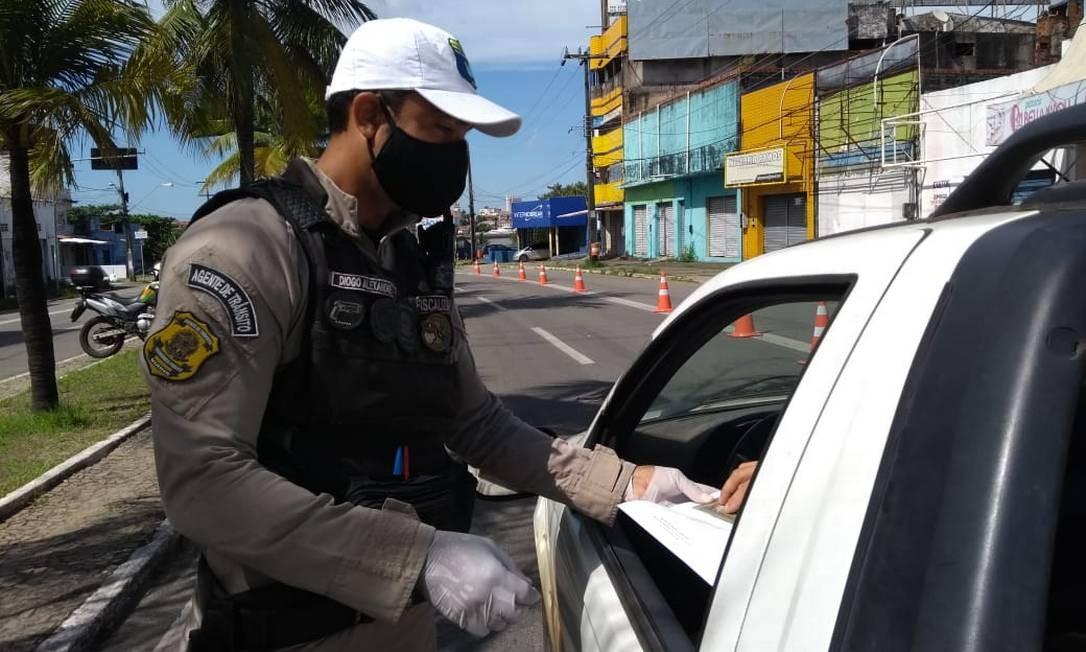 Policial verifica autorização de circulação em blitz em São Luiz; ilha maranhense adotou bloqueio total de acessos nesta terça-feira Foto: Albani Ramos