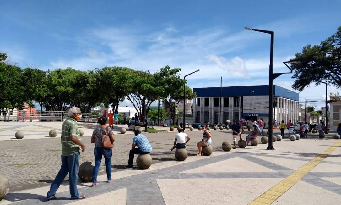 Beneficiários aproveitam gelo baiano no entorno da Praça Deodoro, para esperar, sentados e com distância de segurança, atendimento em agência da Caixa Econômica Federal, em São Luís, Maranhão Foto: Alabani Ramos / Agência O Globo