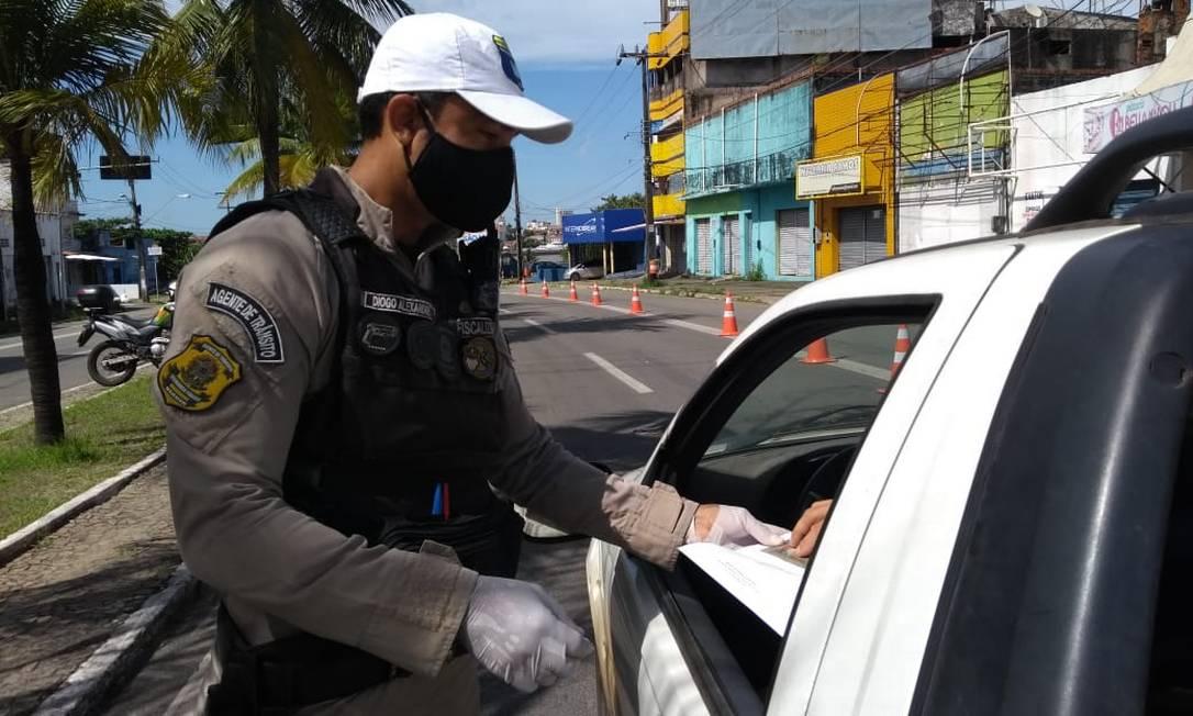 Agente de trânsito confere documentos de motorista em barreira montada em São Luís Foto: Alabani Ramos / Agência O Globo