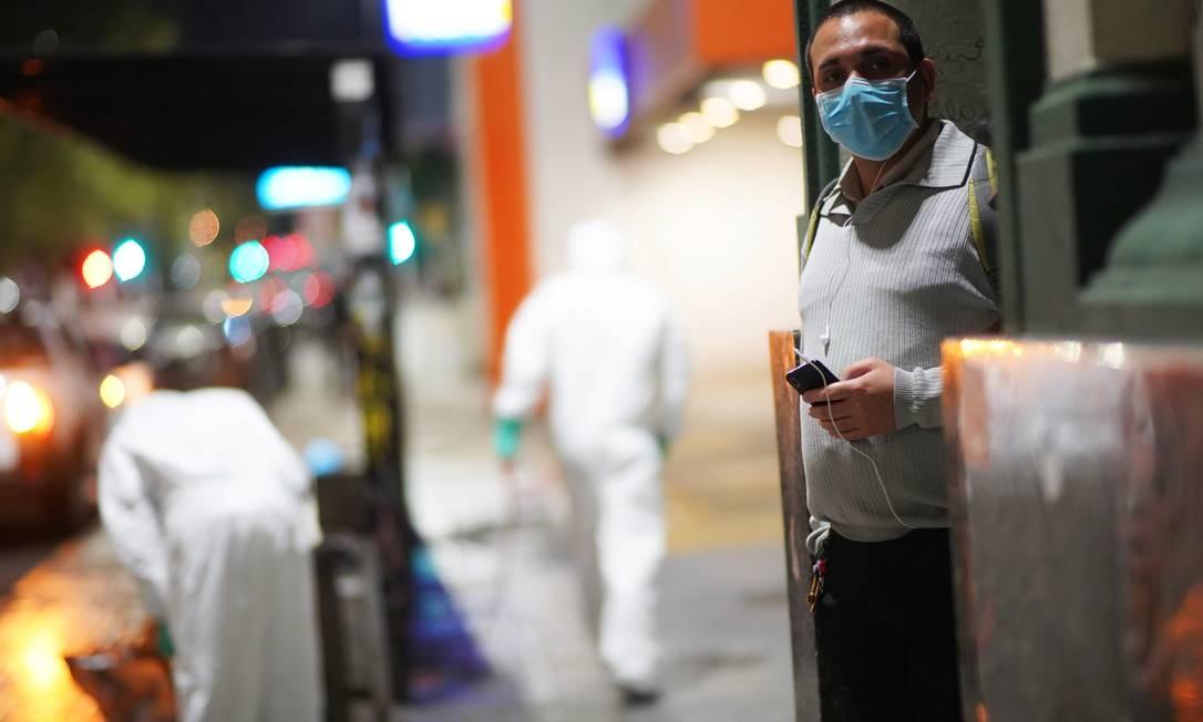 Homem usa máscara enquanto funcionários fazem a limpeza das ruas de Montevidéu, no Uruguai, contra o novo coronavírus Foto: MARIANA GREIF / REUTERS