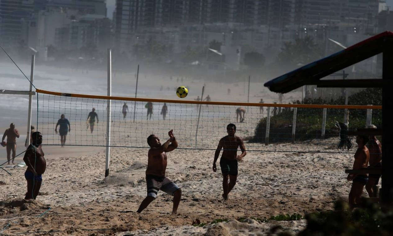 Vôlei a caminhada na areia da praia da Barra da Tijuca na tarde desta terça. Zona Oeste é a região de maior preocupação das autoridades Foto: FABIO MOTTA / Agência O Globo