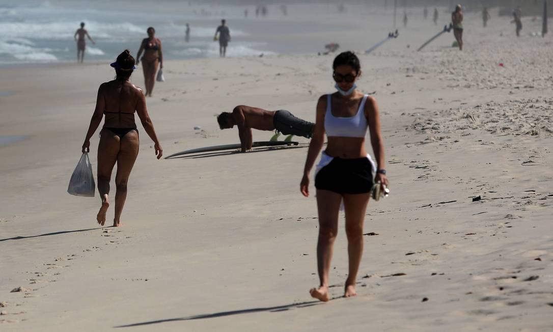 Mulher caminha na areia usando uma máscara de proteção de forma inadequada Foto: FABIO MOTTA / Agência O Globo