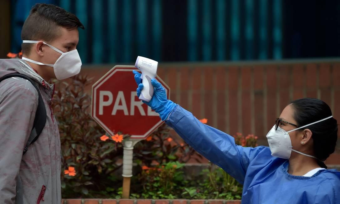 Funcionário de fábrica tem a temperatura conferida antes de começar mais um dia de trabalho na Colômbia Foto: RAUL ARBOLEDA / AFP