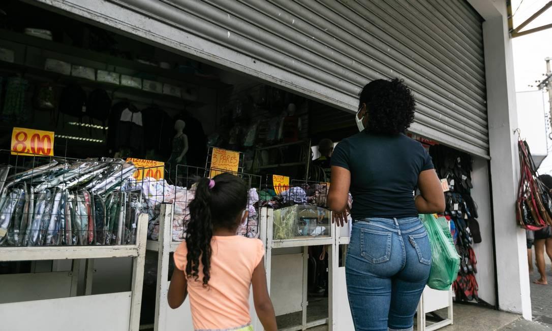 """Lojas de setores não essenciais funcionam com portas pela metade em ruas de Santa Cruz. Descumprimento ao decreto municipal. Ações de """"shutdown"""" parcial, com fechamento de comércio, terão foco na Zona Oeste Foto: BRENNO CARVALHO / Agência O Globo"""