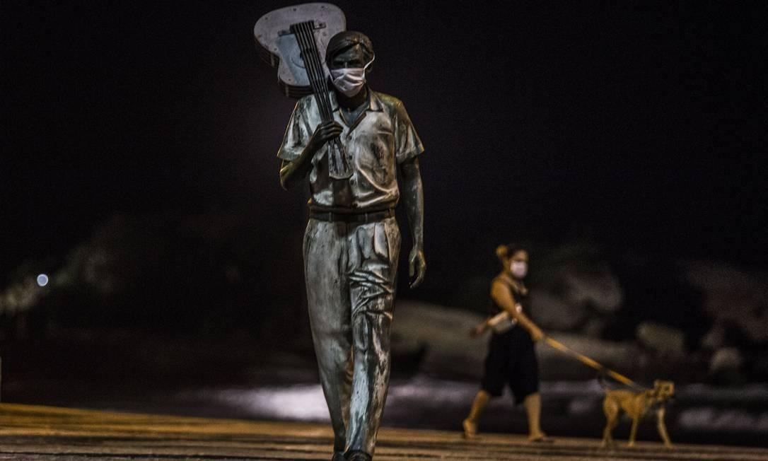 Estátua do compositor Tom Jobim, na orla de Ipanema, no Rio de Janeiro, ganhou uma máscara de proteção. Na cidade cantada pelo grande maestro, o uso do equipamento tornou-se obrigatório em 23 de abril Foto: Guito Moreto / Agência O Globo