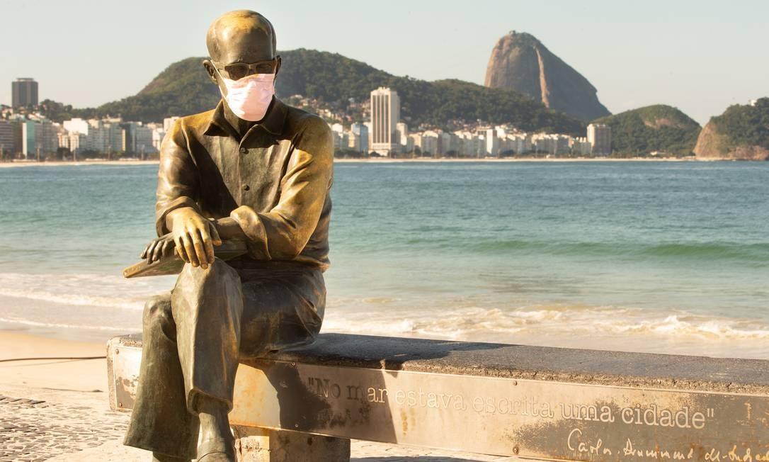A estátua do poeta Carlos Drummond de Andrade, que tanta vezes teve seu óculos arrancado por vândalos, também recebeu máscara facial em meio ao surto do novo coronavírus Foto: Roberto Moreyra / Agência O Globo